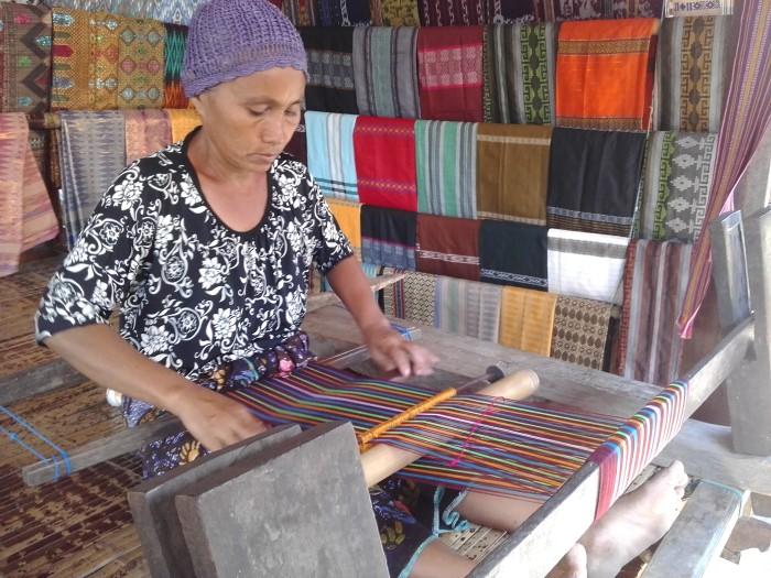 Seorang ibu sedang merajut kain tenun di Desa Sade